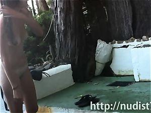 Spy web cam shot of a warm naturist honey tanning on the beach